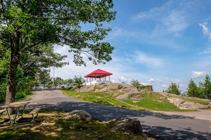 red pavilion at top of lookout point with trees and rock around