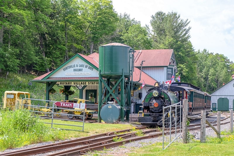 small train station with old steam train and trees behind huntsville ontario