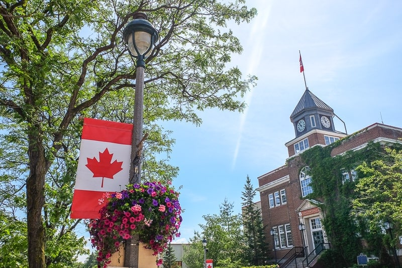 canadian flag on street lamp with old town hall behind things to do in huntsville ontario
