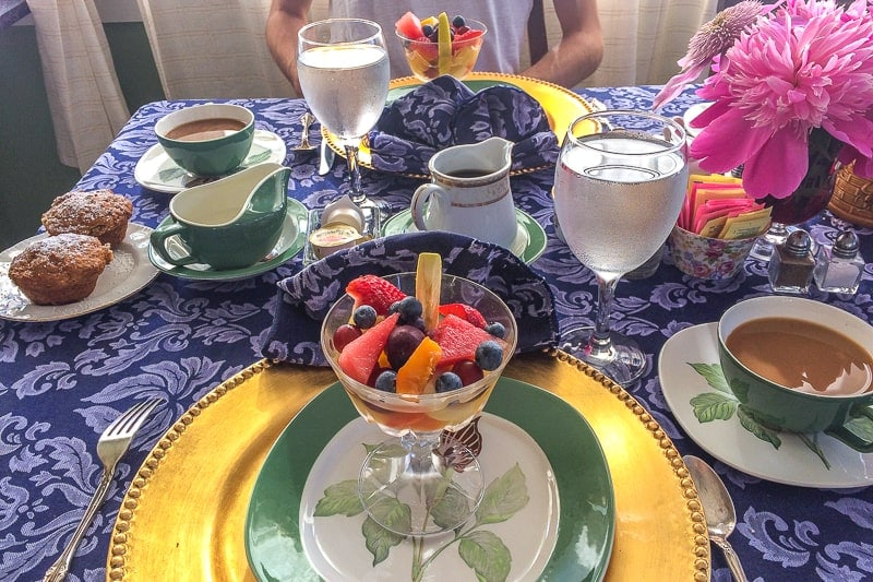 breakfast fruit salad on table with blue cloth and plates