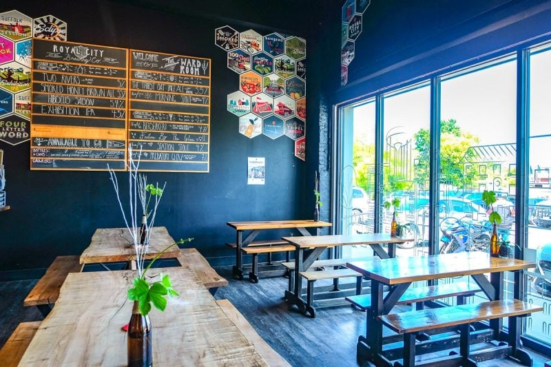 wooden benches are beer on menu on wall inside brewery in guelph