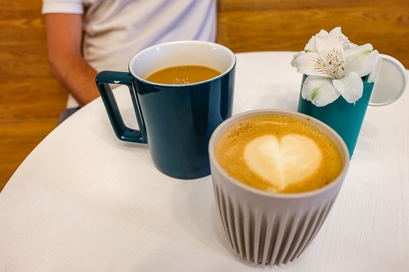 two coffees on white table top with flower at coffee shop in picton ontario