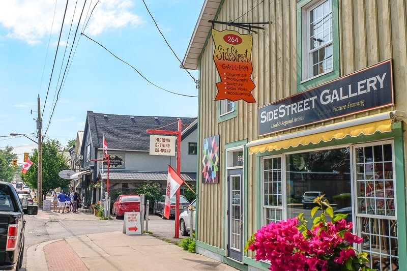 downtown galleries and shops with sidewalk and cars parked along in wellington ontario