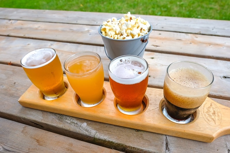 four beer tasting glasses in wooden holder on wooden table with popcorn