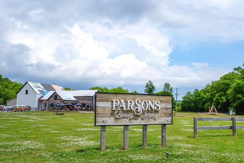 wooden sign for brewery with barn building behind at parsons brewery ontario