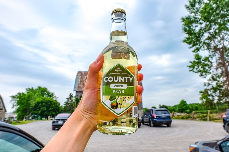 bottle of pear cider held in hand with cars and barn behind the county cider