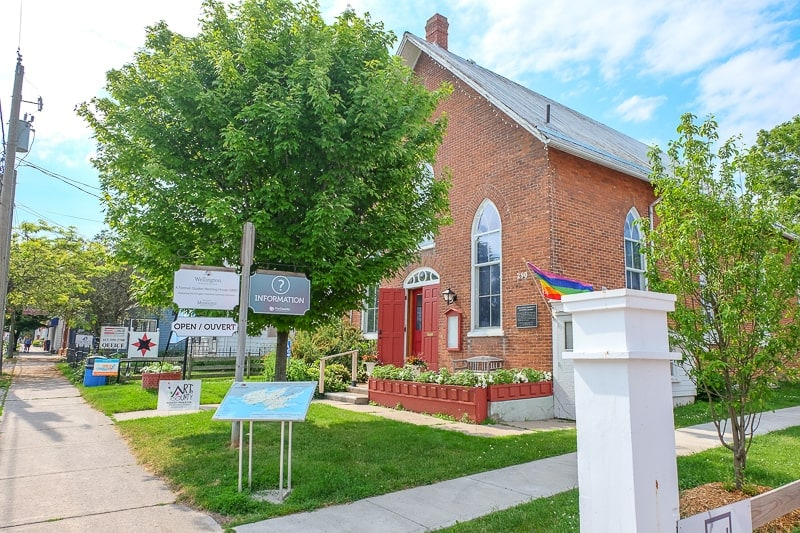 red brick church building with trees and signs in front wellington ontario museum
