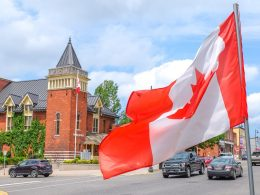 flag by small town building and cars on weekend getaways in ontario
