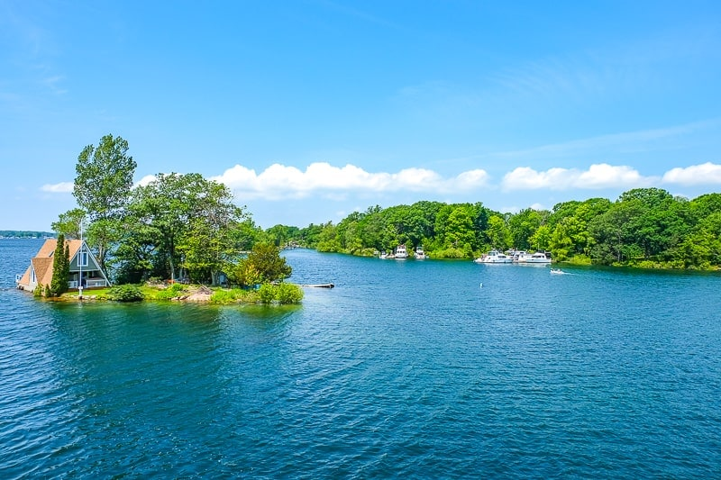 green trees and cabin on small island with lake water around in 1000 islands