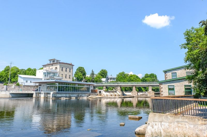 old stone mill by river with bridge over day trips from ottawa