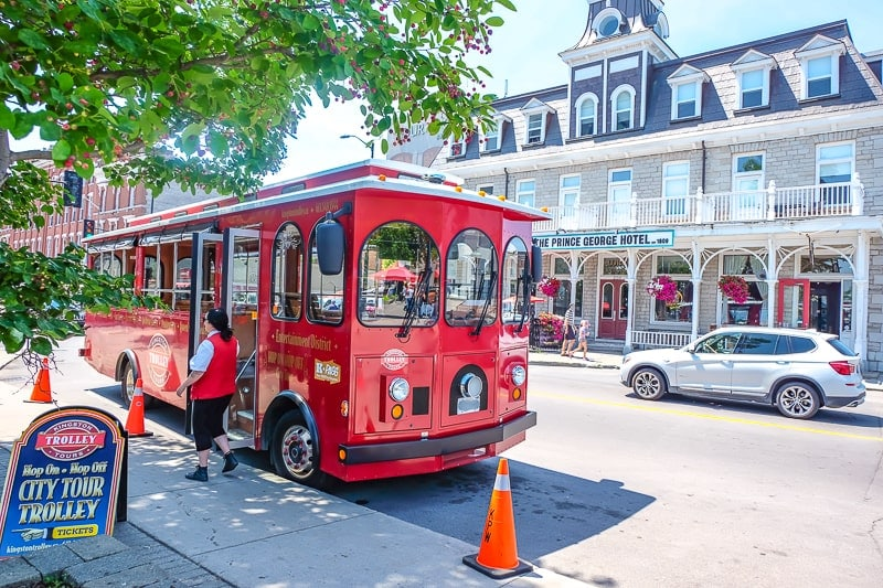 red old trolley car parked on street with old building behind in kingston ontario
