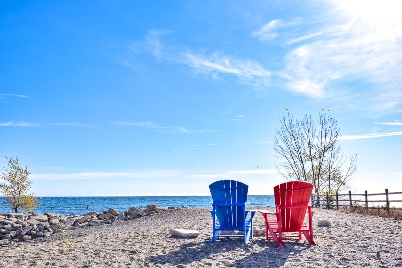 two chairs on rocky beach overlooking blue lake in toronto beaches