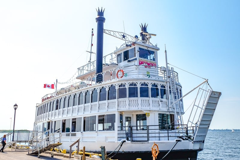 old steamship with canada flag docked at pier in kingston ontario