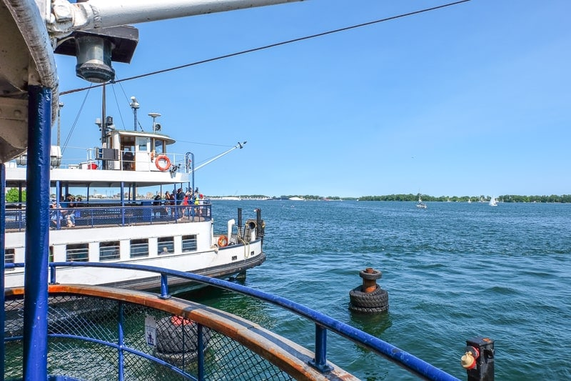 rear of ferry boat with lake water and islands behind in toronto