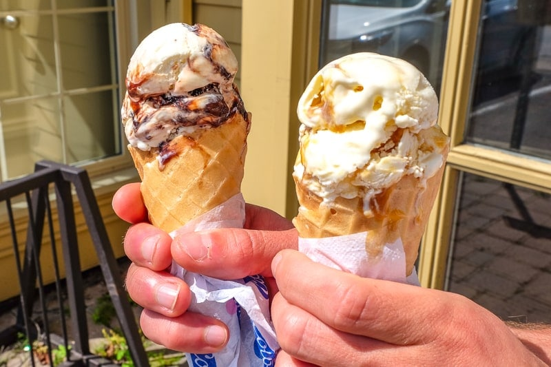 two ice cream cones from cows ice cream held in hand outside NOTL