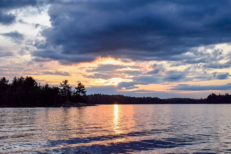 sunset with dark clouds over lake with trees in ontario