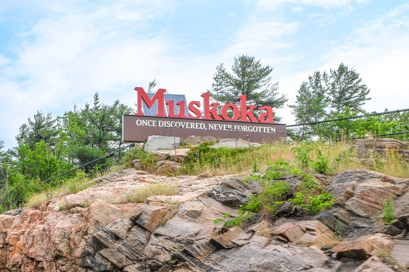 red muskoka sign on rock cliff high above highway