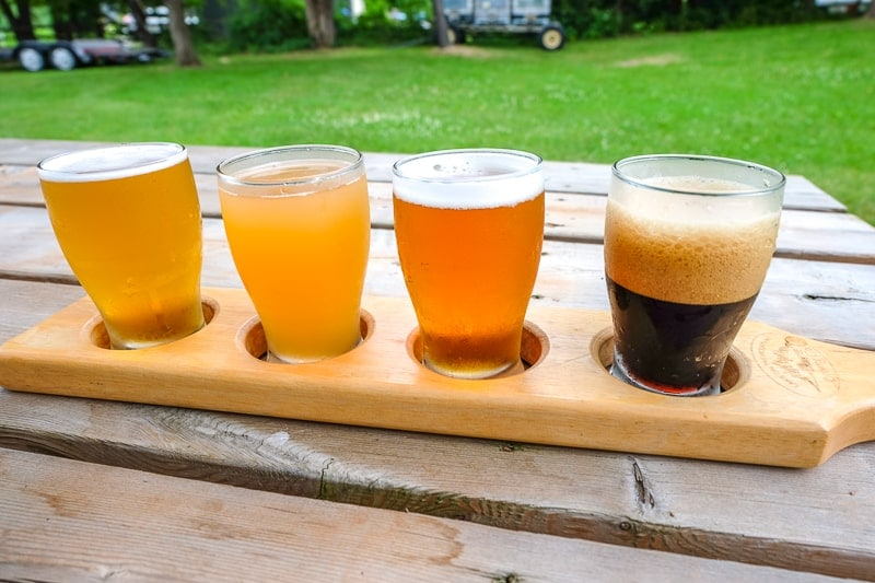 flight of four craft beer glasses in wooden holder