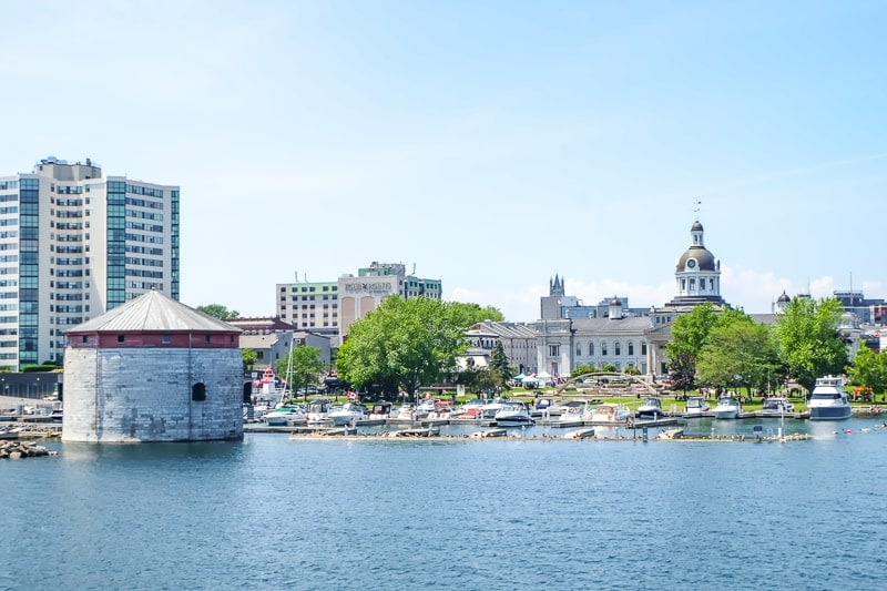 historic waterfront with boats and old town hall in kingston ontario