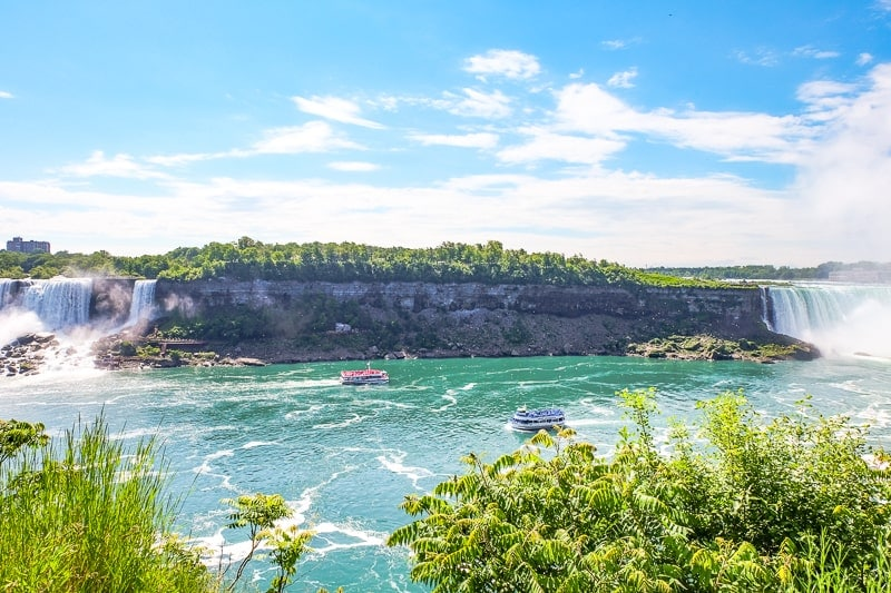 two boats on blue river with niagara falls behind