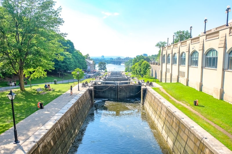 historic rideau canal locks in ottawa beside building and green grass