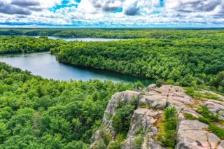 rock cliff with green trees and lakes in distance below at rock dunder hike