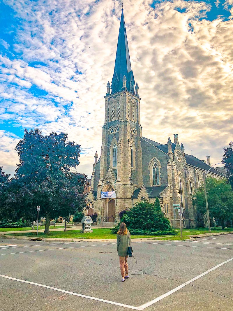 tall church with spire and woman in front standing in road