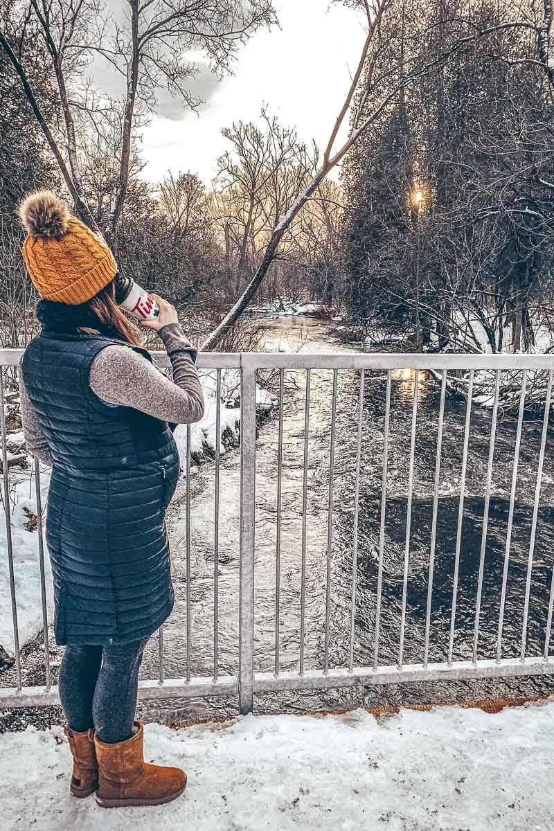 woman in vest standing on bridge over frozen river in winter
