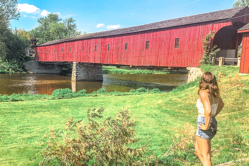 red wooden covered bridge with woman standing beside on green grass