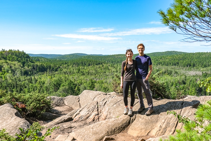 man and woman posing at cliff edge with green valley behind