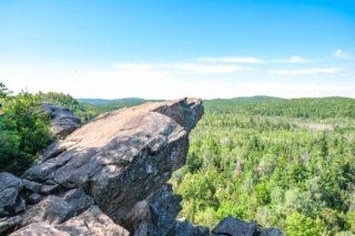 rocky ledge overhanding green trees below in ottawa valley
