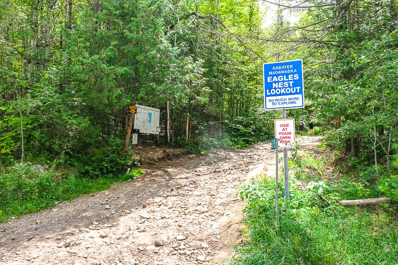 blue sign at trail entrance at edge of forest in calabogie