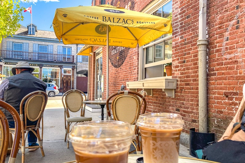 yellow umbrella over patio table at cafe with brick wall