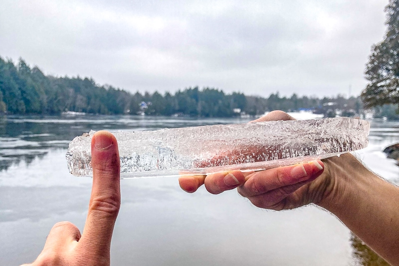 piece of thin ice held in air with hand in front
