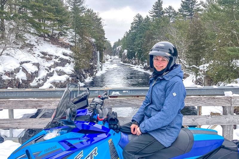 woman with helmet in blue coat sitting on snowmobile with river behind