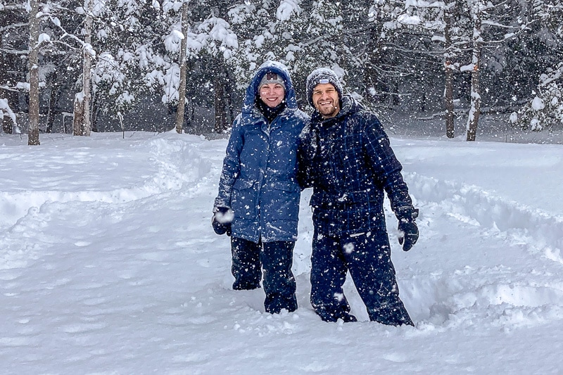 two people standing in deep snow with forest behind