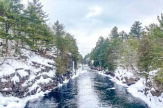 blue river cutting through snowy rock cliffs in ontario